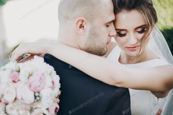 Beautiful stylish wedding couple embracing in summer park