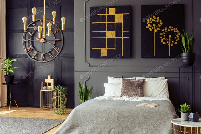 Pflanzen und schwarze und goldene Plakate im grauen Schlafzimmer Interieur mit