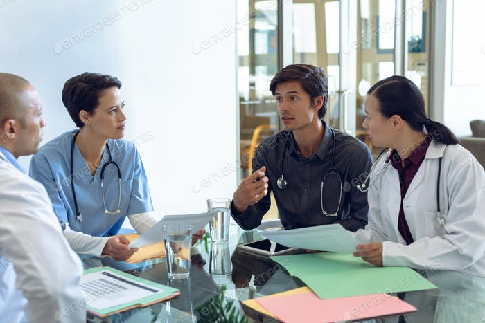 Diverse medical team discussing with each other at the table in hospital.