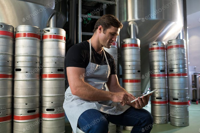 Worker using digital tablet while sitting on keg