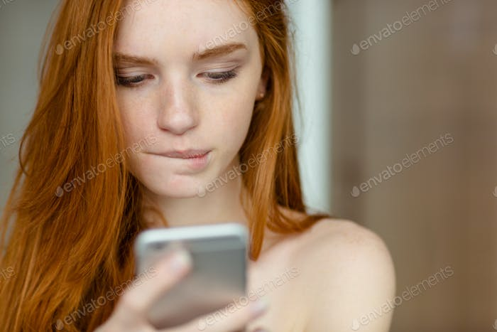 Beautiful redhead woman using smartphone