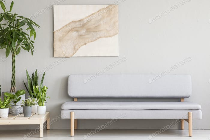 Real photo of a cozy gray couch standing next to a wooden platfo