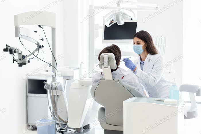 Pretty dentist doctor treating patient in dental clinic