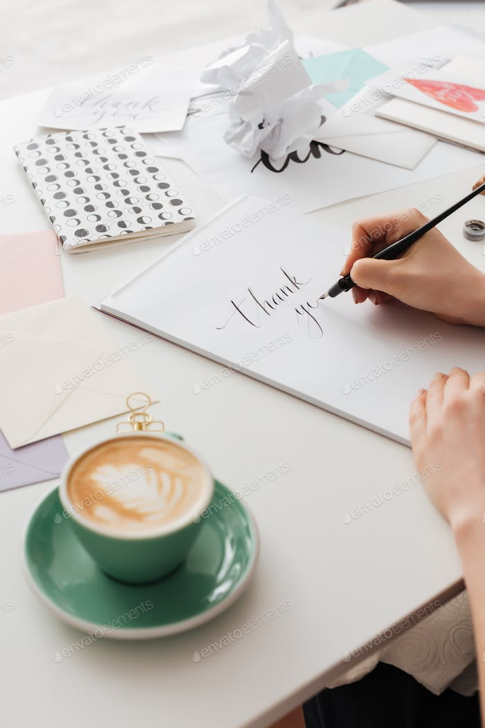 Woman hands holding classic ink pen while writing beautiful notes with cup of coffee on white desk
