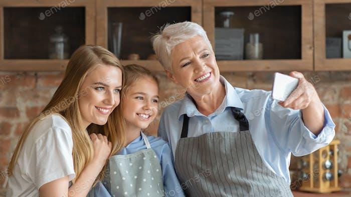 Friendly female family making selfie at kitchen