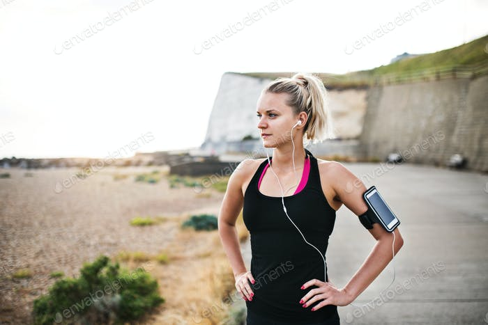 Young sporty woman runner with smartphone standing on the beach outside.