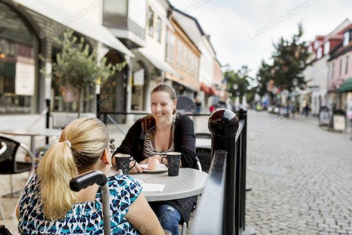 Frau mit Behinderung und ihre Assistentin im Gespräch im Bürgersteig Café