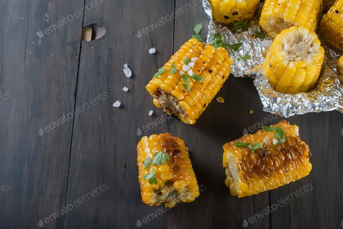 Pieces grilled corn on wooden kitchen board with salt and parsley. The concept of Mexican cuisine.
