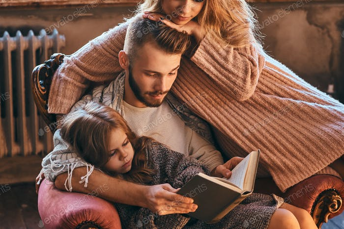 Family togetherness. Mom, dad and daughter reading story book together sitting on the couch