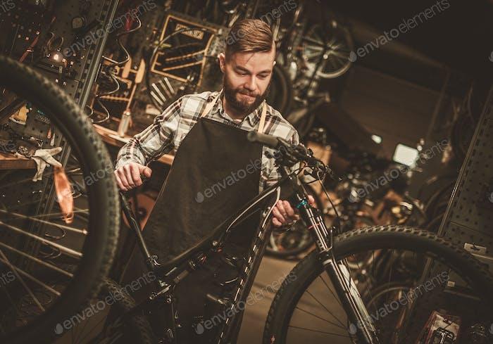 Elegante mecánico de bicicletas haciendo su Trabajo profesional en el taller.