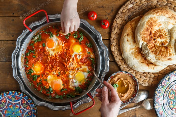 Tasty family breakfast with shakshuka, bread and hummus. Rustic style