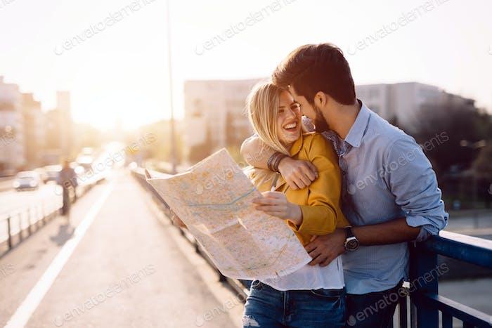 Pareja sonriente en el amor viajando con un mapa al aire libre