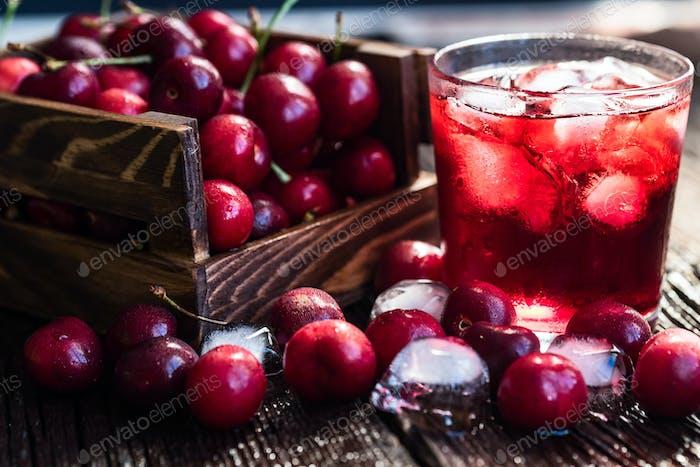 Fresh cherries in a wooden box, ice, cherry juice
