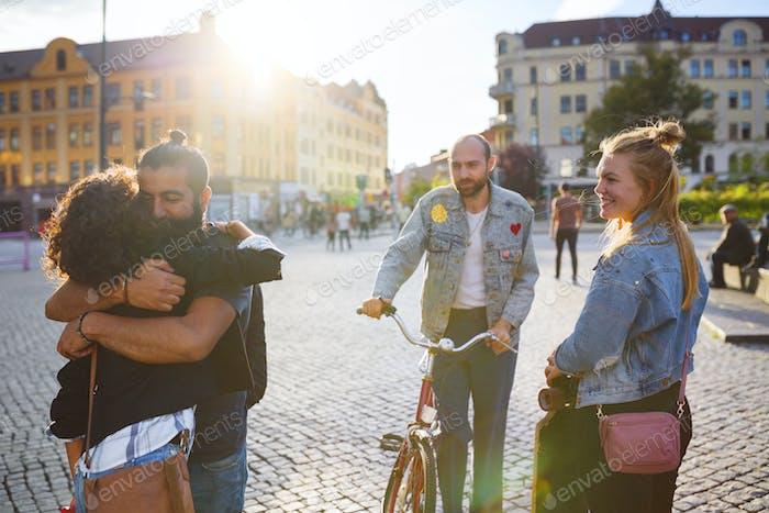 Zwei Freunde umarmen und andere Freunde lächeln