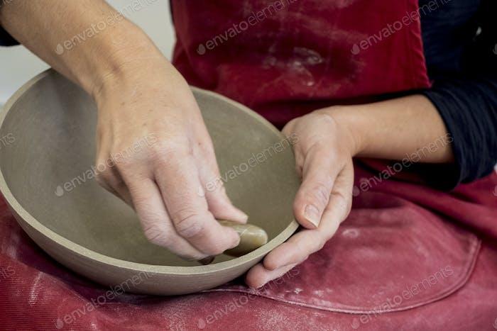 Nahaufnahme von Keramik-Künstler trägt rote Schürze Arbeit auf Tonschüssel.