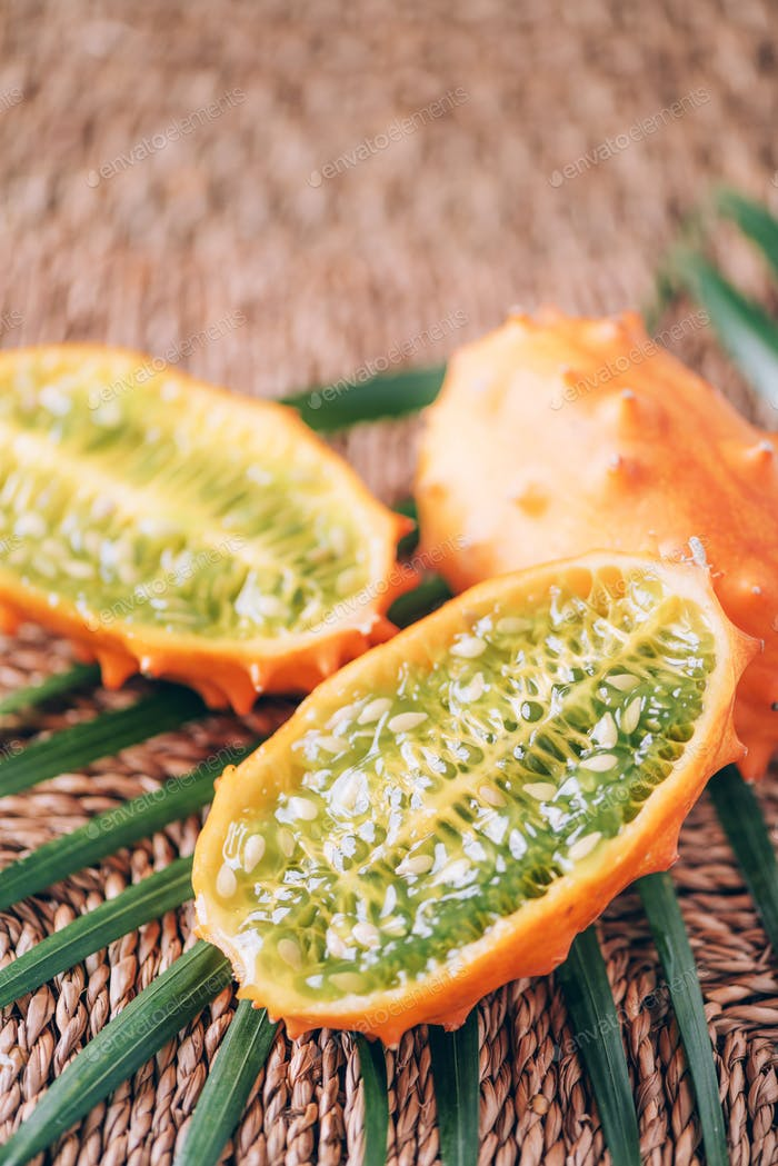 Kiwano or african horned melon with palm leaves on rattan background. Cutted hedged gourd, african