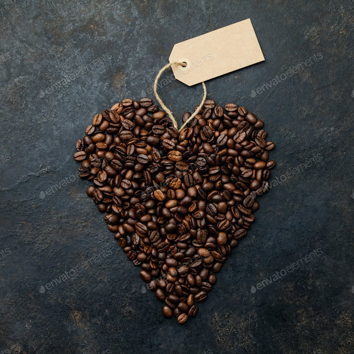 Coffee beans in shape of heart on dark rustic background