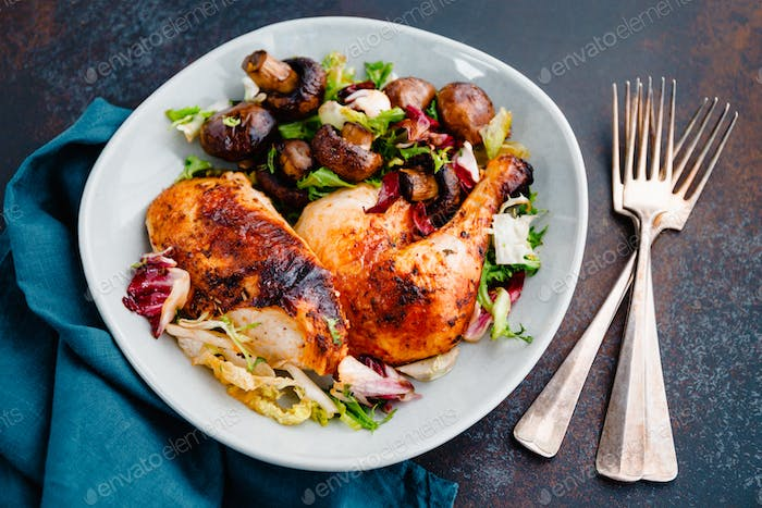 Roasted chicken leg and breast with fresh salad and champignons on a plate.