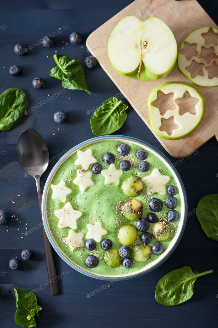 healthy green spinach smoothie bowl with blueberry, banana stars