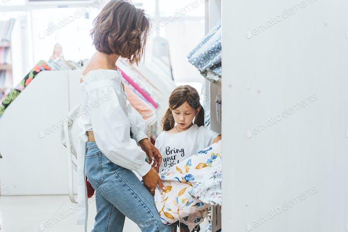 Mutter und Tochter im Stoffladen wählen Stoff