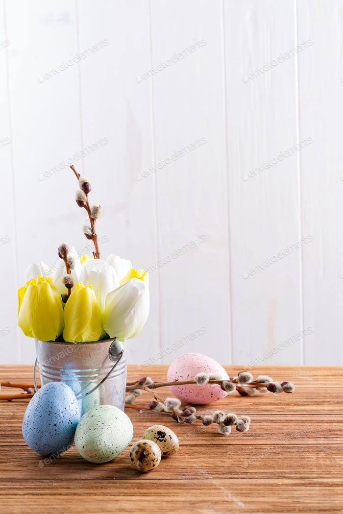 Happy Easter card with fresh spring tulips flowers in a bucket and handmade painted eggs on a wooden