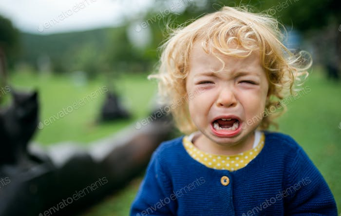 Portrait of small girl outdoors in garden, crying