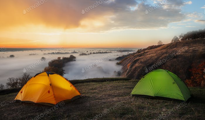 Orange and green tents over river sheltered by mist