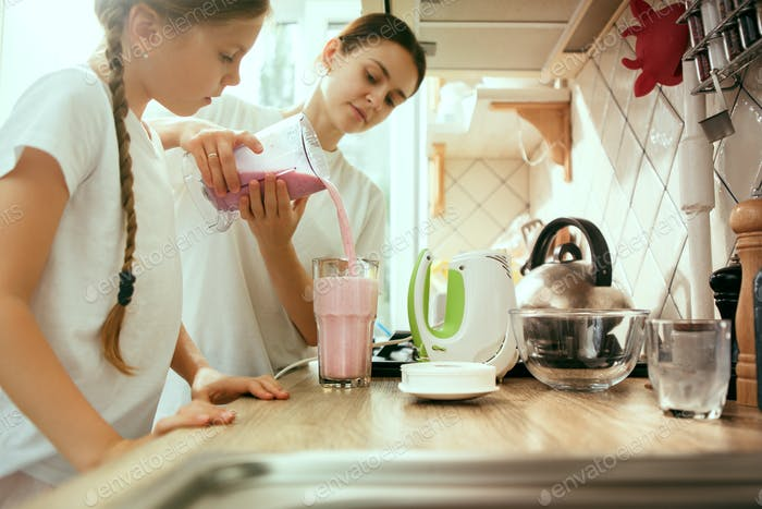 The happy smiling caucasian family in the kitchen preparing breakfast