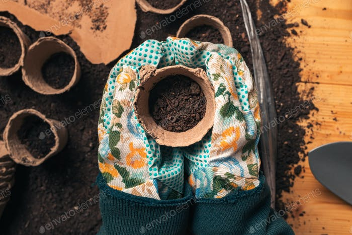 Top view of florist holding soil in flowerpot