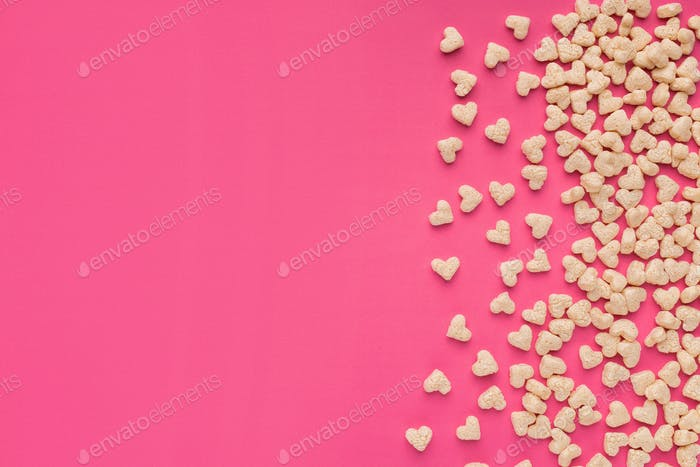 Top view of cereals in heart form on pink background