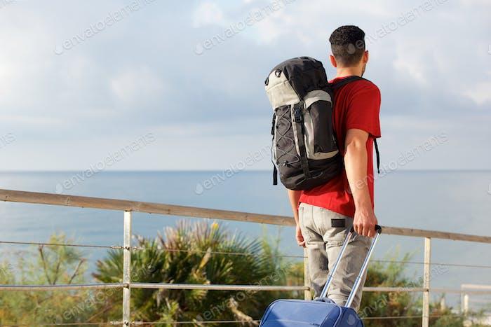 Mann Reisen mit Rucksack und Koffer