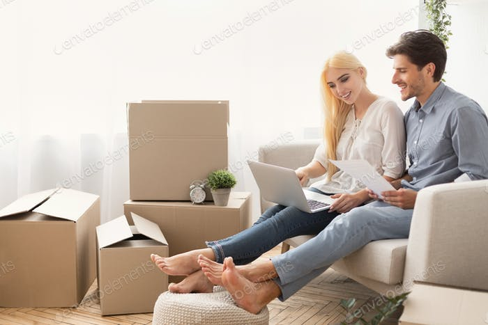 Couple Planning Design Project Sitting With Laptop On Couch