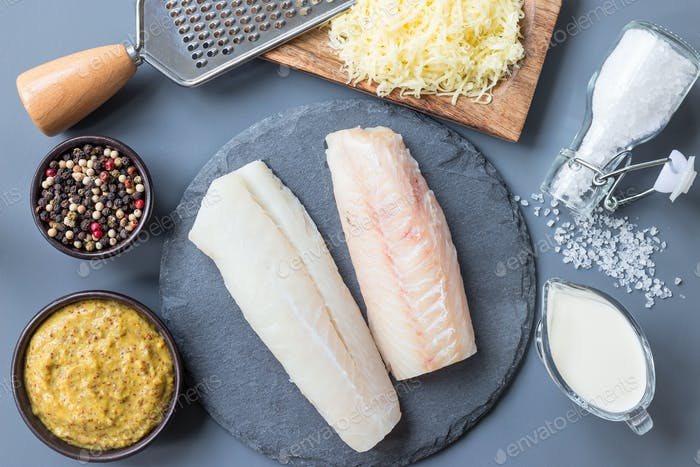 Fresh raw cod fillet with ingredients, pepper, salt, mustard, cr