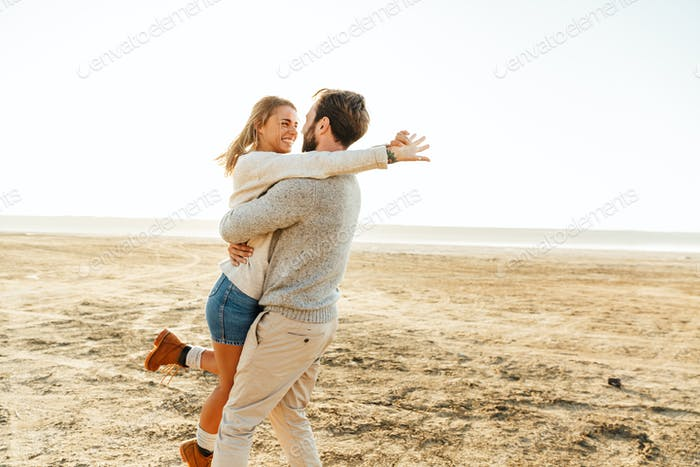 Beautiful young couple standing at the sunny beach