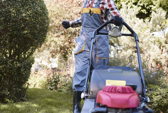 Unrecognizable man turning on mower