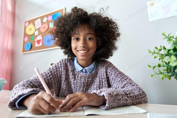 Glückliches afrikanisches Mädchen, das auf Webcam-Fernunterricht online schaut, Kopfschuss.