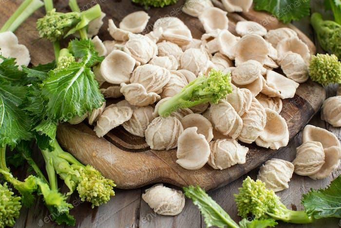 Raw homemade Orecchiette pasta and turnip greens