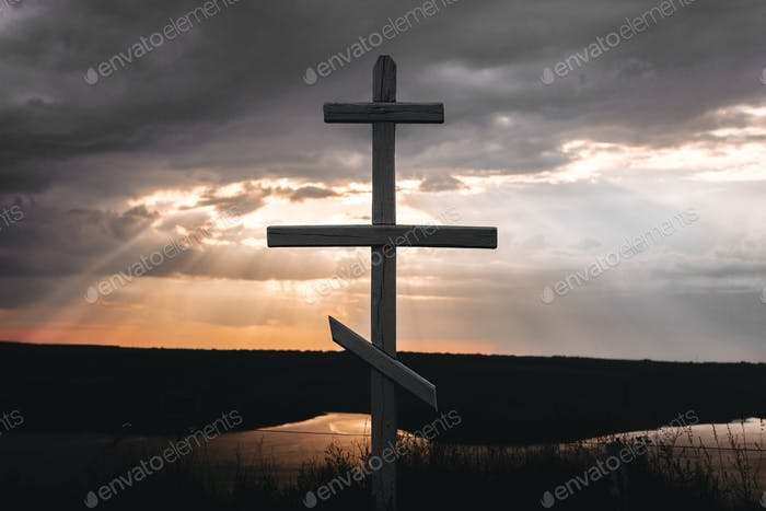 Cross In sunset light from dark clouds