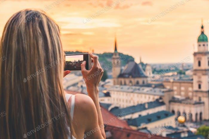 Tourist macht ein Foto von schönen Sonnenuntergang in Salzburg Österreich