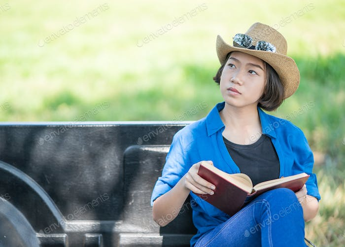 Woman wear hat and reading the book on pickup truck-13