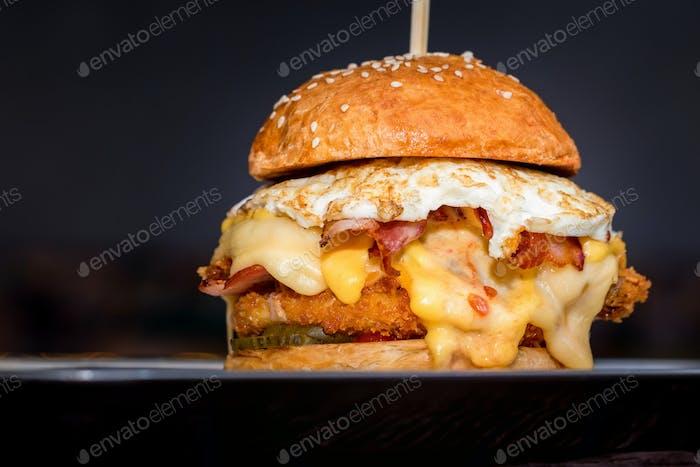Nahaufnahme großer schmackhafter Burger mit Käse und Ei auf Tablett serviert