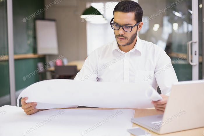 Casual architect studying his blueprints in the office
