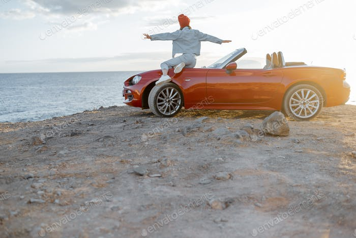 Woman traveling by car on the rocky coastline