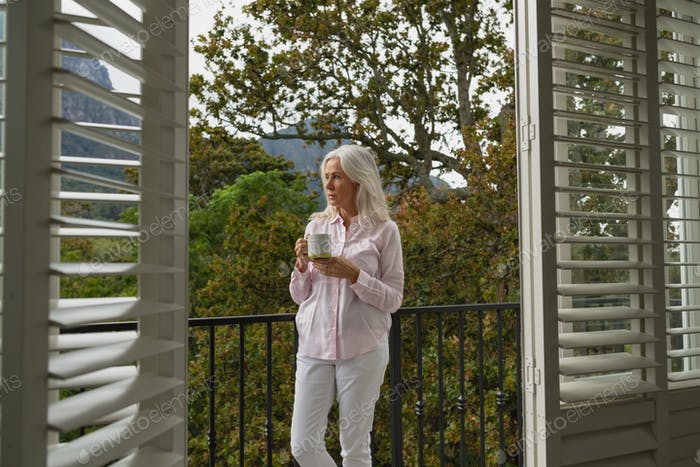 Thoughtful active senior Caucasian woman standing with coffee mug on the balcony at home.