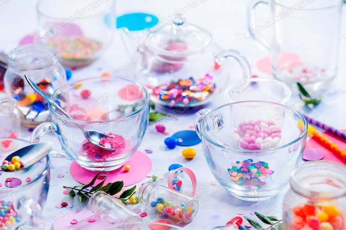 Glass tea cups in the morning light. Birthday party concept with sprinkles, confetti, candies