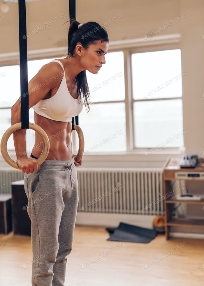 Sports woman working out with gymnastic ring