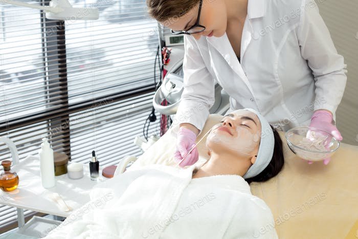 Female Cosmetologist Applying Face Mask