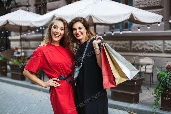 Young cheerful woman in red dress and beautiful smiling lady in