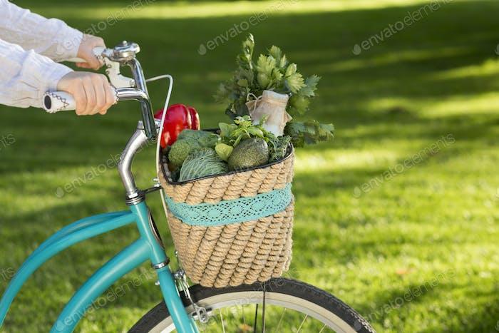 Woman riding on bike with fresh farm vegetables