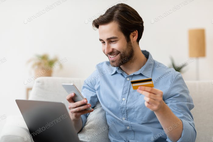 Smiling Guy With Phone And Credit Card Shopping Online Indoor
